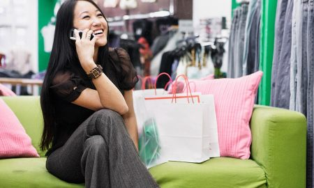 Young woman talking on her cell phone while shopping --- Image by ฉ Ned Frisk/Blend Images/Corbis