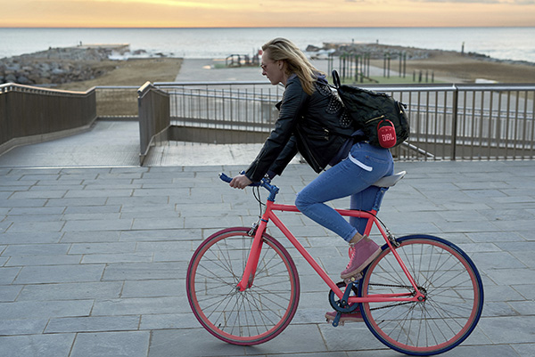 Side view of blonde woman with backpack on bike riding against morning seascape.