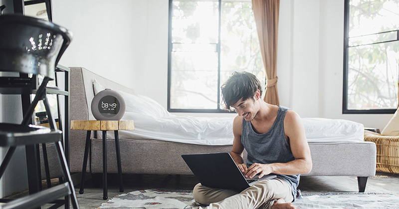 Young man uses his laptop in a bedroom.